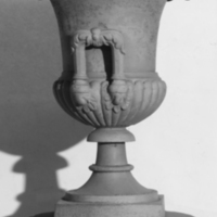 "Pair of cast-iron, campana-form urns, the bodies semi-lobed with foliated handles, the scalloped rims with modified egg-and-dart motif, on ringed, tapered socles and integral square bases, marked ""Wood & Perot Philadelphia."""