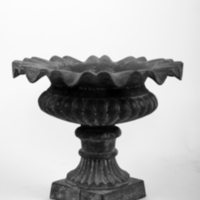 Pair of cast-iron, campana-form urns, the bodies shallow and semi-lobed, with fluted, ringed, and tapered socles and unusual wavy rims<br /><br />