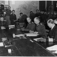 The Chief of Staff of the German Army, signing the document of unconditional surrender for all German forces, bring the war in Europe to a close, May 7, 1945.